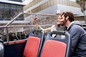tourist couple travel selfie on open top tour bus in city