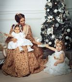 Young mother and her two little daughters near Christmas tree in living room. Retro style.
