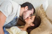 Cute couple kissing on couch at home in the living room