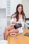 Pretty brunette pouring herself a coffee at home in the kitchen