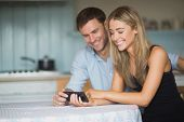 Cute couple using smartphone together at home in the kitchen