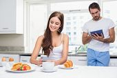 Young couple using technology at breakfast at home in the kitchen