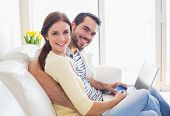 Cute couple relaxing on couch with laptop at home in the living room