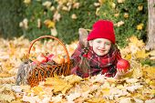 little girl in autumn park with apple basket