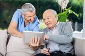 Male nurse and senior man smiling while using tablet computer at nursing home porch