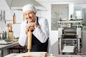Portrait of happy male chef holding rolling pin at counter while preparing pasta in commercial kitchen