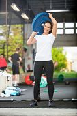 Full length portrait of fit woman lifting barbell plate