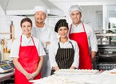 Portrait of confident chef team standing together at counter in commercial kitchen