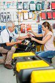 Full length of salesman assisting female customer in selecting tools at hardware store