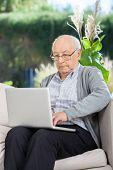 Senior man surfing on laptop at nursing home porch