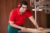 Young male carpenter cutting wooden plank with bandsaw in workshop