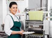 Portrait of confident female chef holding ravioli pasta tray by machine at commercial kitchen