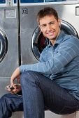Portrait of young man listening to music while sitting against washing machine at laundromat