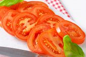 detail of tomato slices and kitchen knife on white cutting board
