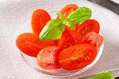 tomato salad with basil on white tablecloth
