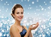 people, holidays, christmas and glamour concept - smiling woman in evening dress with diamond over snowy city background