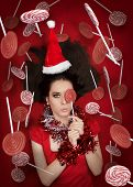 Funny Christmas Girl Holding a Candy Surrounded by Lollipops