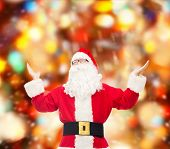 christmas, holidays and people concept - man in costume of santa claus with raised hands over red lights background