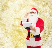 christmas, holidays and people concept - man in costume of santa claus with notepad over yellow lights background