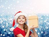 christmas, holidays, childhood and people concept - smiling girl in santa helper hat with gift box over snowy city background