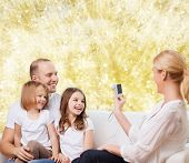 family, holidays, technology and people - smiling mother, father and little girls with camera over yellow lights background