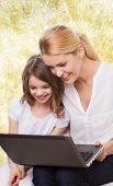 family, childhood, holidays, technology and people concept - smiling mother and little girl with laptop computer over yellow lights background
