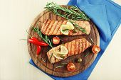Grilled salmon with spices on cutting board on wooden background