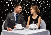 celebration, christmas, holidays and people concept - smiling couple at restaurant over black snowy background