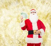 christmas, holidays, winning, currency and people concept - man in costume of santa claus with euro money over yellow lights background