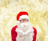 christmas, holidays and people concept - man in costume of santa claus blowing on palms over yellow lights background
