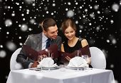 food, christmas, holidays and people concept - smiling couple with menus at restaurant over black snowy background