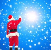 christmas, holidays and people concept - man in costume of santa claus pointing finger from back over blue snowy background