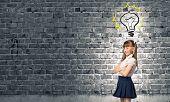 Cute schoolgirl and electrical bulb above head