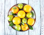 Ripe citrus with green leaves on plate on wooden background