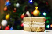Gift box on Christmas tree lights background