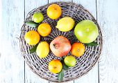Ripe citrus on plate on wicker background