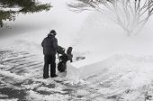 stock photo of snow shovel  - Male clearing snow from parking lot during winter storm - JPG