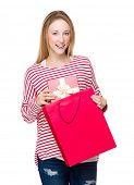 Woman take gift box from shopping bag