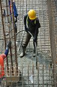 stock photo of vibrator  - A construction worker using a concrete vibrator at a construction site in Selangor - JPG