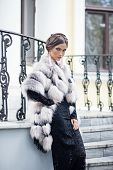 Fashion Model Posing In A Fur Coat On A Stairs