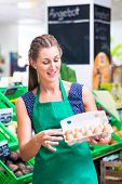 Female organic Supermarket clerk filling up egg storage racks in fresh department