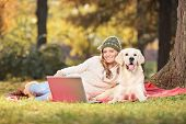 Woman enjoying a picnic with her dog in park in the autumn