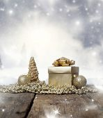 Christmas background with decorations and gift box on wooden table and winter landscape in the background