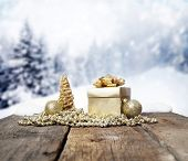 Christmas decorations and gift box on wooden table - firs in the background