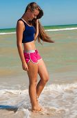 Young beautiful girl athlete on the beach