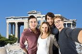 Four tourists taking a selfie in front of an old Greek temple during their vacation