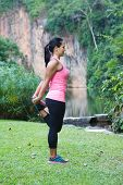 Sporty woman stretching her thigh, exercising in the park