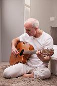 Mature Man Playing Guitar At Home