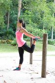 Sporty woman stretching her thigh on a bar, exercising in the park