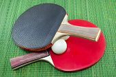 foto of ping pong  - Two vintage table tennis rackets and two ping pong balls on a green background - JPG